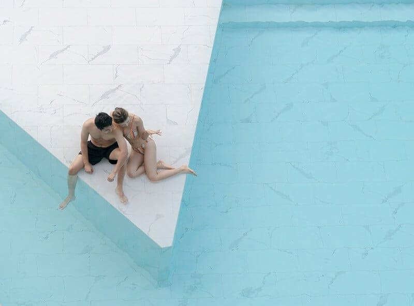 pareja sentada en una piscina