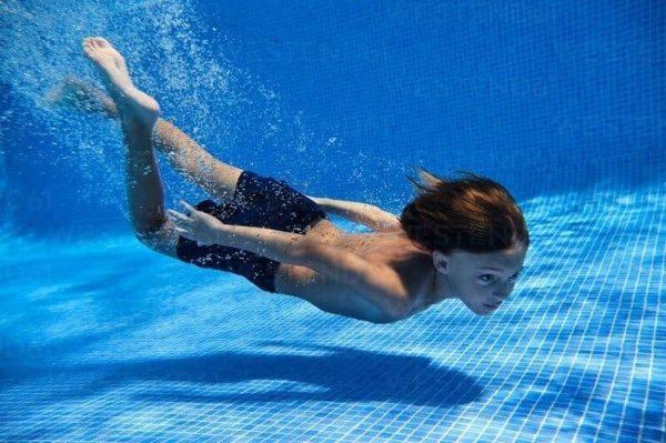 chico nadando en la piscina
